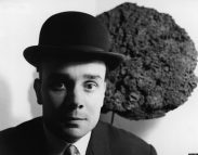 Black and white portrait of French artist Yves Klein (1928 - 1962) in a bowler hat as he stands in front of one of his Blue Sponge Sculptures, France, late 1950s. The first public display of these sculptures, which were made from different sized sponges that had been dyed blue, was on June 15, 1959 at the Galerie Iris Clert in Paris, France. (Photo by Express Newspapers/Getty Images)